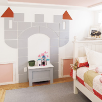 A dimensional castle on the wall holds stuffed animals or other toys.