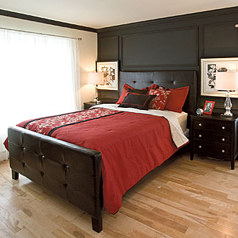 Dark wood furniture and walls make a striking contrast with the red bedding set and light wood floor
