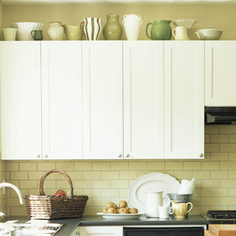 Decorative containers on wall cabinets provide extra storage