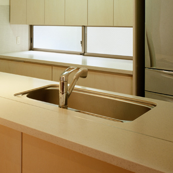 Large kitchen sink under solid-surface countertop