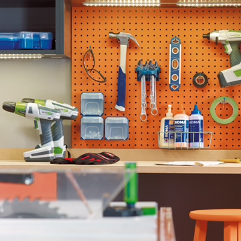 Pegboard panels and hooks keep tools tidy.