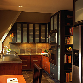 Kitchen with stainless steel counters and glass- fronted cabinets